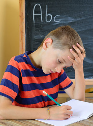 Young boy trying to do his homework.